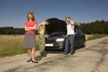 Deutschland, Bayern, Drei Freunde mit kaputten Auto