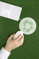 Person mit Computer-Maus, Maus-Pad mit Recycling-Symbol