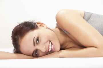 Junge Frau liegt auf dem Bett, Lächeln