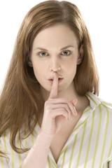 Junge Frau mit Finger auf die Lippen