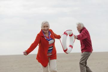 Deutschland, St. Peter-Ording, Nordsee, älteres Paar, Senioren, ziehen Rettungsring