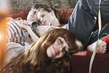 Deutschland, Berlin, jungen Menschen und Frauen entspannt auf der Couch nach der Party
