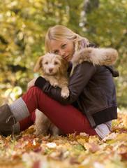 Österreich, Junge Frau sitzt mit Hund auf Herbstblättern, Lächelnd