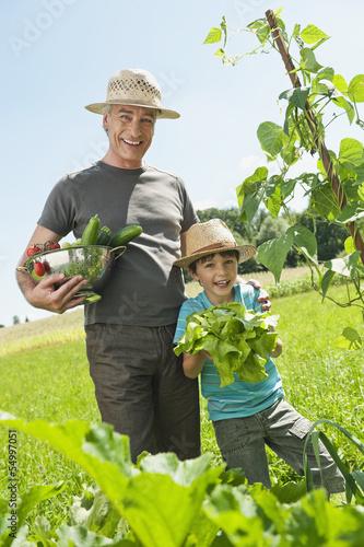 Deutschland, Bayern, Großvater mit Enkel im Gemüsegarten
