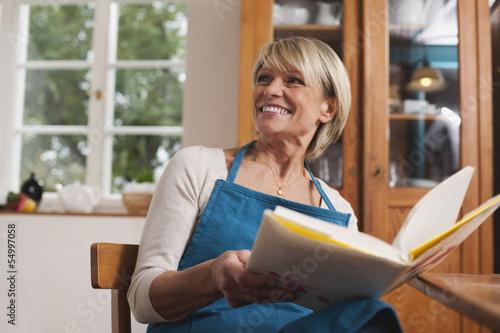 Deutschland, Kratzeburg, erwachsene Frau mit Kochbuch
