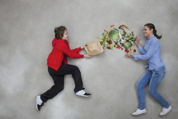 Frau und Junge balancieren Gemüse