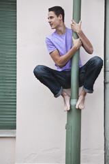 Deutschland, Berlin, Junge sitzt auf Ampel-polig