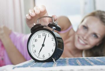 Italien, Toskana, junge Frau im Bett, Hotelzimmer, Wecker ausschalten