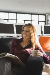 Geschäftsfrau im Büro mit Tasse und Zeitung, Lächeln