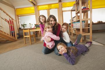 Deutschland, Babyzimmer, Kindergärtnerin und Kinder spielen zusammen