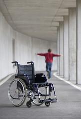 Österreich, Mondsee, Junger Mann balanciert, mit Rollstuhl im Vordergrund
