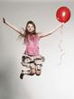 Mädchen springt mit Ballon
