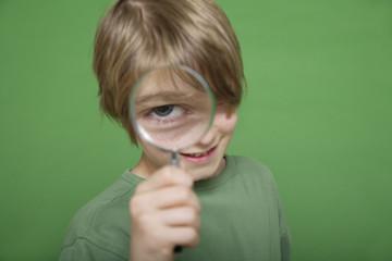 Nahaufnahme von Junge, Blick durch Lupe vor grünem Hintergrund