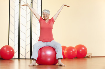 ältere Frau, Seniorin sitzt auf Gymnastikball, Lächelnd
