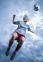 Deutschland, Augsburg, Fußballspieler springend in die Luft, Kopfball