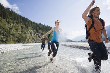 Deutschland, Bayern, Tölzer Land, Junge Freunde, die durch Fluss laufen