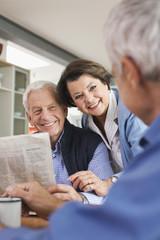 Deutschland, Leipzig, Senior, Rentner liest Zeitung, Mann und Frau lächeln