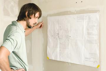 Junger Mann studiert Bauplan