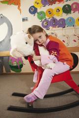 Deutschland, Mädchen sitzt auf einem Schaukelpferd, mit Teddybär