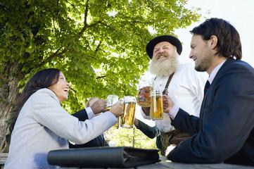 Deutschland, Bayern, Oberbayern, Menschen in Biergarten stoßen an