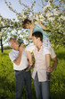 Deutschland, Baden Württemberg, Tübingen, Drei Generation Familie, Junge sitzt auf Vaters Schultern, Blick auf Blumen