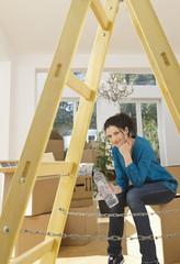 Deutschland, Bayern, Gröbenzell, Frau sitzt in der Nähe einer Holzleiter in Haus