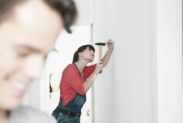 Deutschland, Köln, Junge Frau hämmert , Wohnungsrenovierung mit Mann im Vordergrund