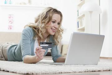 Deutschland, Bayern, München, Frau auf dem Boden liegend, mit Laptop und Shopping mit Kreditkarte