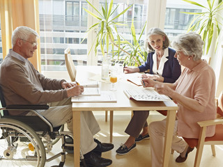 Deutschland, Köln, Mann im Rollstuhl, mit Frauen im Pflegeheim