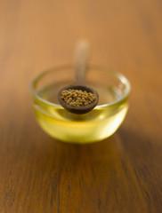 Senfkörner in hölzernem Löffel auf Schüssel Öl
