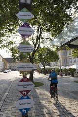 Österreich, Steiermark, Bad Radkersburg, Erwachsene fahren Fahrrad mit Straßennamen Zeichen
