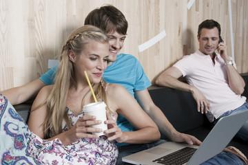 Deutschland, Köln, Paare im Café mit Laptop, Mann im Hintergrund mit Handy