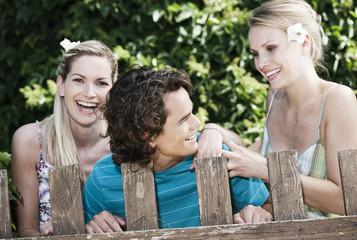 Italien, Toskana, Magliano, Junger Mann und Frau, die hinter Holzzaun stehen