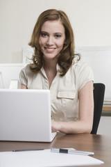Deutschland, München, junge Frau im Büro, mit Laptop