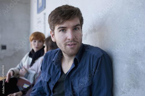 Deutschland, Leipzig, junger Mann mit Studenten im Hintergrund