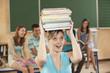Deutschland, Emmering, Junge Frau mit Stapel Bücher mit Studenten im Hintergrund
