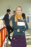 Deutschland, Leipzig, Junge Frau hält ein Buch, Studenten stehen im Hintergrund