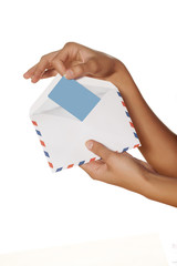 woman's hand pulls a credit card from the envelope