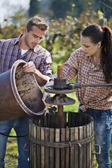 Kroatien, Baranja, Junger Mann und Frau neben Weinpresse