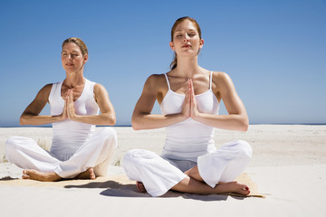 Zwei Frauen machen Yogaübungen am Strand