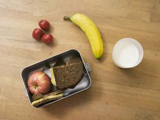 Lunch-Box auf dem Tisch, mit Sandwich, Obst und ein Glas Milch