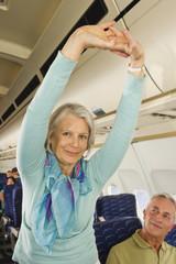 Deutschland, München, Bayern, Stretching ältere Frau, Seniorin und Mann in der Economy-Klasse Verkehrsflugzeug