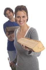 Frau hält Holz, Mann im Hintergrund