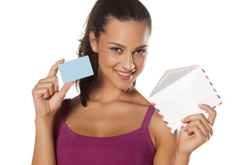 beautiful girl holding an envelope and showing her credit card
