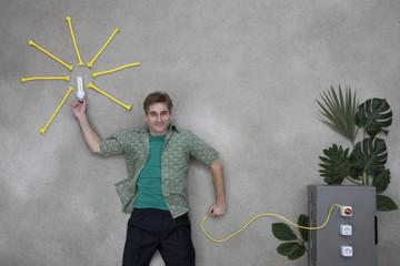 Mann hält Glühbirne und ist durch ein Stromkabel mit einer Pflanze verbunden