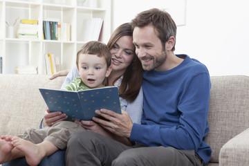 Deutschland, Bayern, München, Parents Lesebuch mit Sohn im Wohnzimmer