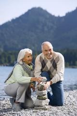 Deutschland, Bayern, Walchensee, älteres Paar häufen Steine auf