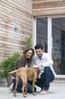 Junges Paar spielt mit Hund auf der Terrasse