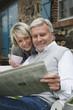 Deutschland, Kratzeburg, älteres Paar, Senioren sitzt auf der Terrasse des Landhauses und liest Zeitung