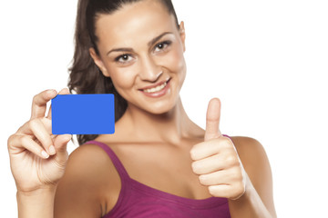 smiling girl holding her credit card and showing thumbs up